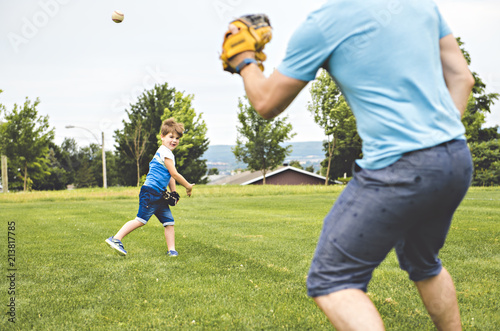 Photo Handsome dad with his little cute sun are playing baseball on green grassy lawn