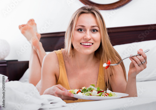 Foto op Plexiglas Akt Blond woman in underwear sitting in the bed and enjoying a salad