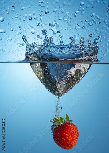 Fototapeta kuchenna owoce w wodzie   jeden-truskawka-jagody-spada-do-wody-na-niebieskim-tle