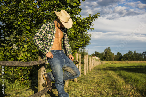 Fotografia Portrait of sexy farmer or cowboy in hat with unbuttoned shirt on muscular torso