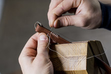 Close Up Of Craftsman Making Brown Leather Camera Strap, Hand Stitching Two Pieces Of Leather, Held In A Clamp.