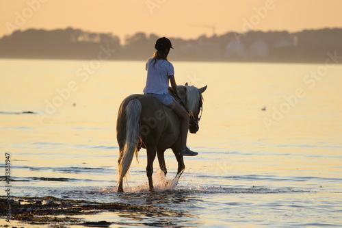 Tuinposter Paardrijden junge Frau reitet mit Pferd am Strand an der Ostsee