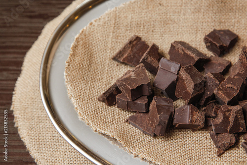 Fényképezés cioccolato su iuta sopra un piatto elegante sopra una tavola di legno