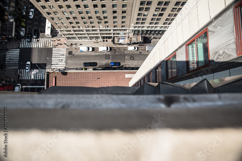 Downwards view from the ledge of a building in New York City with street below i Wallpaper Mural