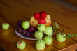 fresh sweet fruits on a plate on a wooden table