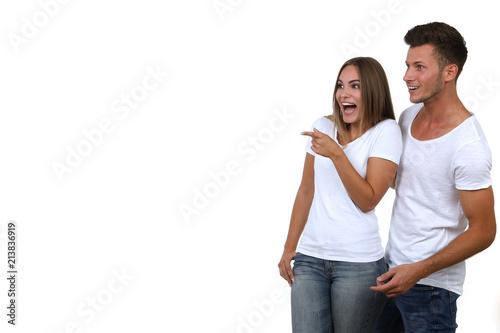 Photo  Hübsches junges Paar blickt erstaunt und zeigt in eine Richtung