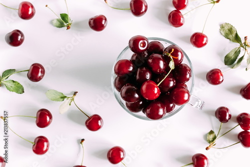 Juicy cherry in a glass bowl. Ripe cherry berries and leaves isolated on white background. Berry summer background. Flat lay, top view, copy space