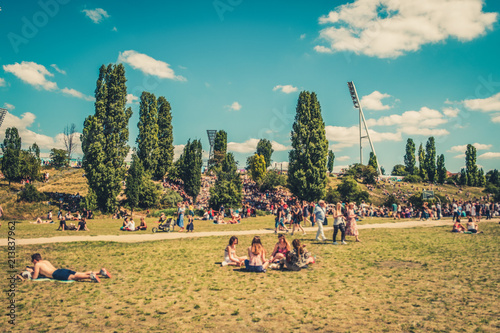 Obraz Cityscape blur concept - People enjoying sunny summer day on meadow in crowded Park (Mauerpark) in Berlin City - fototapety do salonu