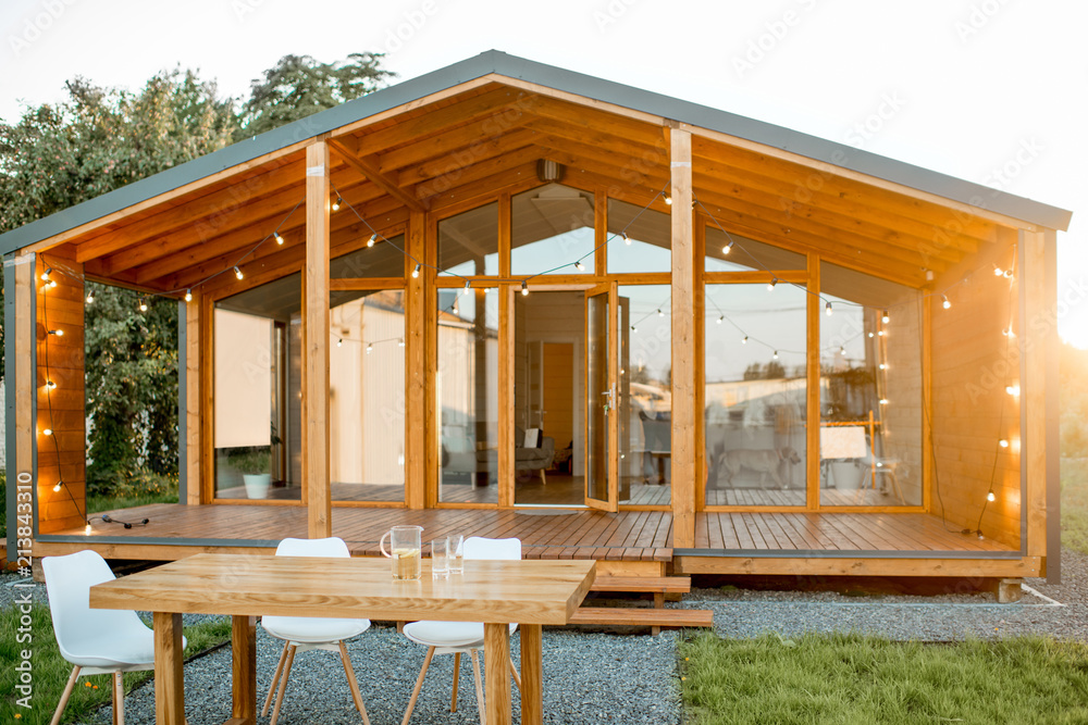 Fototapeta Beautiful backyard of the wooden country house with table for dining