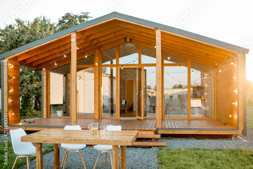 Obraz Beautiful backyard of the wooden country house with table for dining - fototapety do salonu