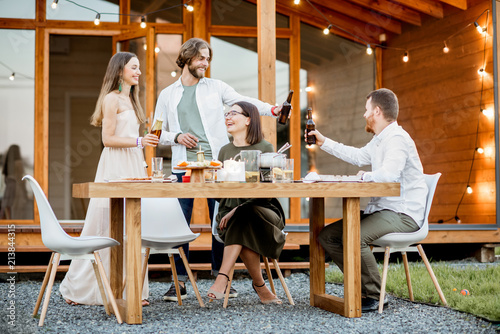 Young friends having fun during the dinner on the backyard of the modern wooden Canvas Print