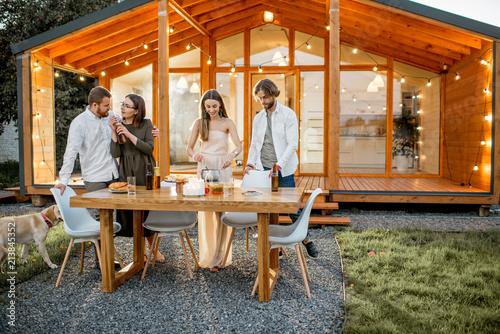 Fotografie, Tablou Four friends enjoying evening time having a dinner on the backyard of the modern