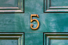 House Door Number 5 In Bronze On An Older Wooden Painted Green Door