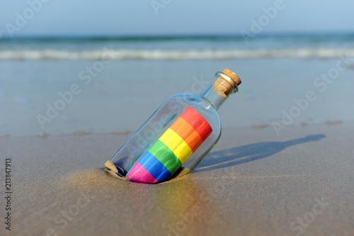 Fotografía  Mensaje del orgullo gay en una botella a la orilla del mar