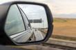 Asphalt road reflected in car mirror.