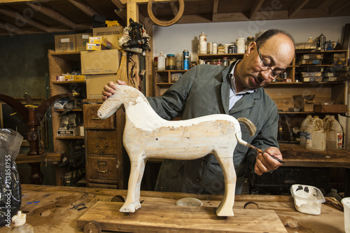Business owner of antique restoration and wood carving studio at his workbench painting model of wooden horse in New York City, USA