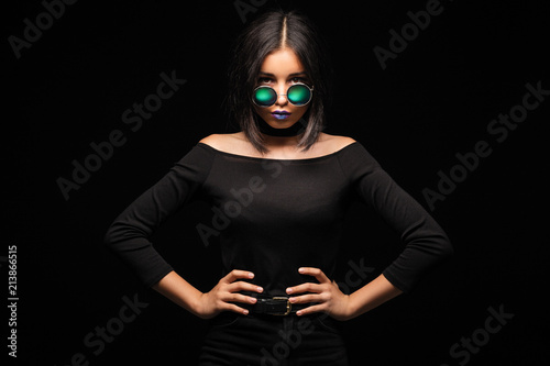 Photo Portrait of cool crazy brunette fashionable girl in sunglasses, casual hairdo on black background