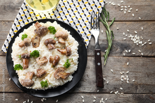 Plate with delicious risotto and mushrooms on wooden table, top view