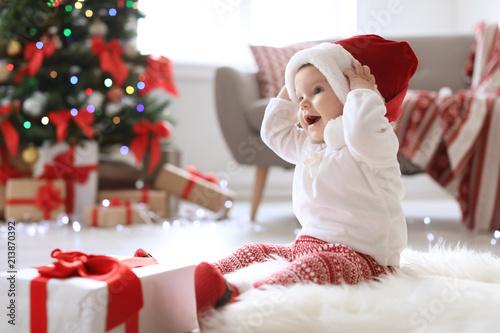 Fototapeta Cute baby in Santa hat on floor at home. Christmas celebration obraz