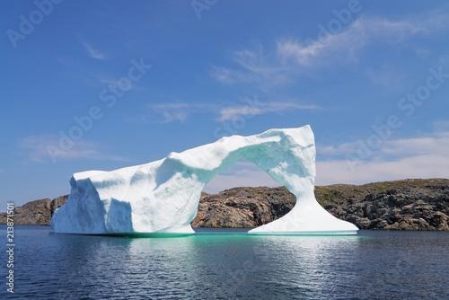 Obraz na płótnie Iceberg in front of a rocky island, Newfoundland and Labrador