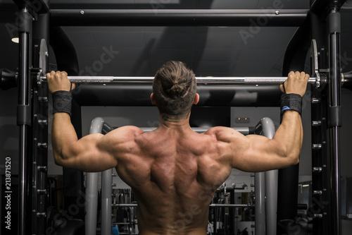 Fotografia Hombre fuerte con grandes músculos haciendo dominadas en el gimnasio de espaldas