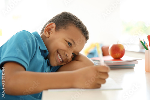 Fotografie, Obraz  Cute little child doing assignment at desk in classroom