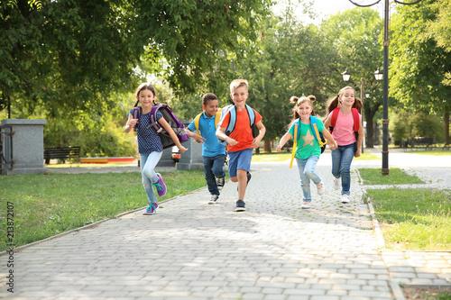 Fotografía  Cute little children with backpacks running outdoors