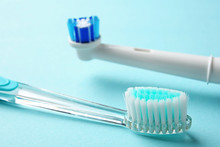 Manual And Electric Toothbrushes On Color Background, Close Up. Dental Care