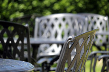 Close Up Of A Wrought Iron Chair, With Other Similar Chairs And Tables In The Out Of Focus Background On A Lovely Sunny Day