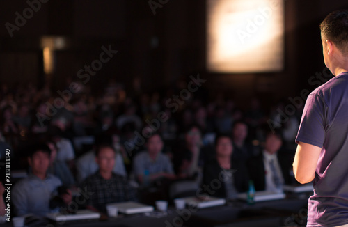 Fototapety, obrazy: Presenter Speaking to Audience People in Conference Hall Auditorium. Presentation Stage. Blurred De-focused Unidentifiable Audience and Presenter. Technology. Casual Attire Presenter.