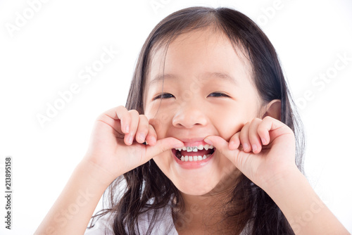 Photo Young Asian girl child showing silver amalgam tooth sealant over white backgroun