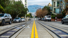 Street Of San Francisco, California USA. Alcatraz In The Background. Trolley Tracks And Parked Cars In  The Scene.