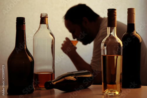 Fotografija  silhouette of anonymous alcoholic person drinking behind bottles of alcohol