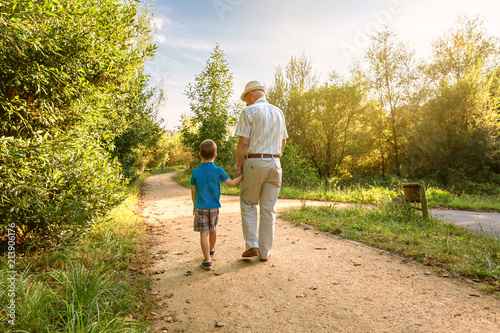 Obraz Back view of grandfather with hat and grandchild walking on a nature path - fototapety do salonu
