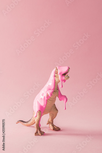 Fotografie, Tablou  Pink paint dripping on dinosaur toy. Creative minimal concept.