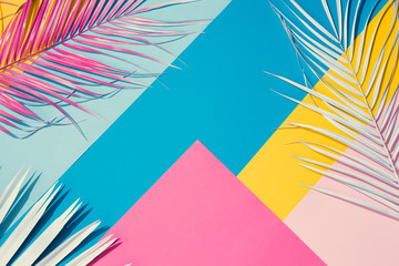Tropical bright colorful background with exotic painted tropical palm leaves. Minimal fashion summer concept. Flat lay.