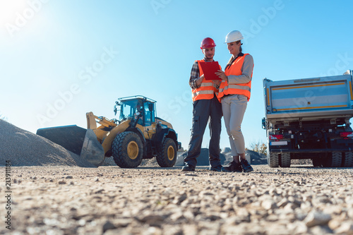 Worker and engineer on earthworks construction site planning, woman and man