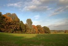 Krajobraz Jesienny Z Resztką Zielonej Trawy Na łące, Drzewami Z Kolorowymi Liśćmi  I Sunącymi Po Niebie Malowniczymi Chmurami - Długie Naświetlanie