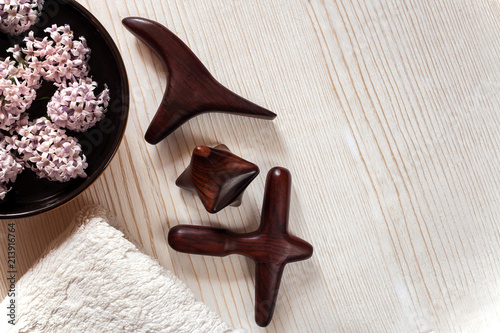 Staande foto Spa SPA and massage concept. Wooden massage sticks, terry towel, bowl with flowers on wooden background.