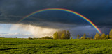 Fototapeta Tęcza - a beautiful, colorful rainbow against the background of a dangerous, stormy sky over a rural farm