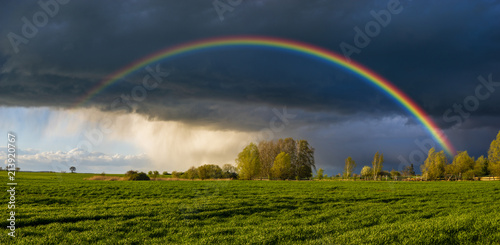 a beautiful, colorful rainbow against the background of a dangerous, stormy sky over a rural farm