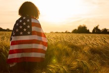 Young Woman Wrapped In USA Flag In Field At Sunset