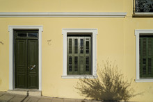 Scene Of Beautiful Urban Building Facade Background In Pastel Cream Yellow Plaster Paint Wall, Olive Green Wooden Entry Door And Windows With Tree Shadow