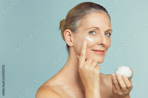 Obraz na plátně Mature woman applying skin cream on face