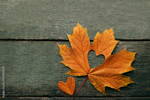 Dry maple leaf with heart on grey wooden table