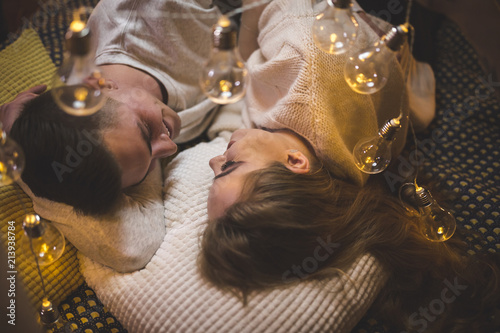 Romantic young couple cuddling in bed with fairy lights