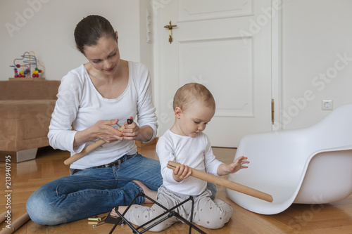 Mother and daughter assembling a chair at home