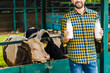 cropped image of smiling farmer holding bottles of cow milk near stable