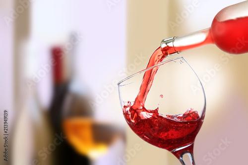 Wino czerwone wlewane do kieliszka, lampka do wino.