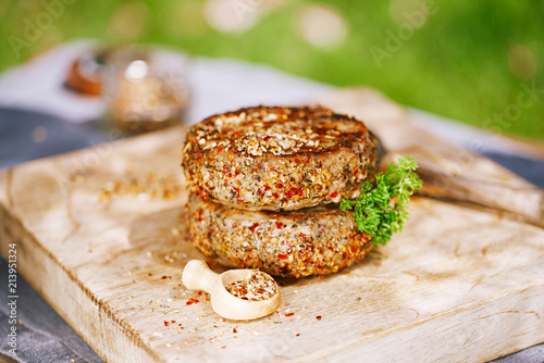 lamb burgers spiced by mint and lamb rub on wood board